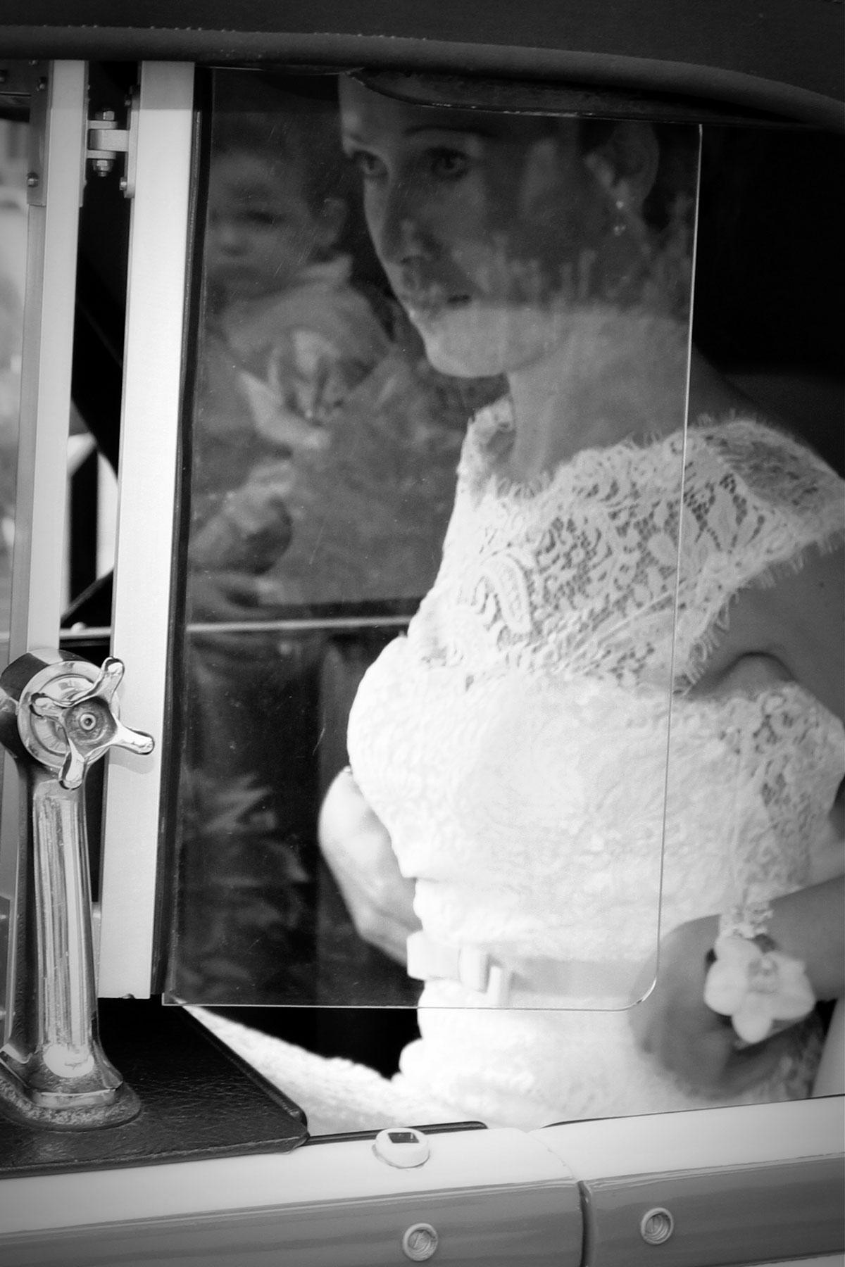 La mariée à travers la vitre de sa voiture mariage robe de mariée